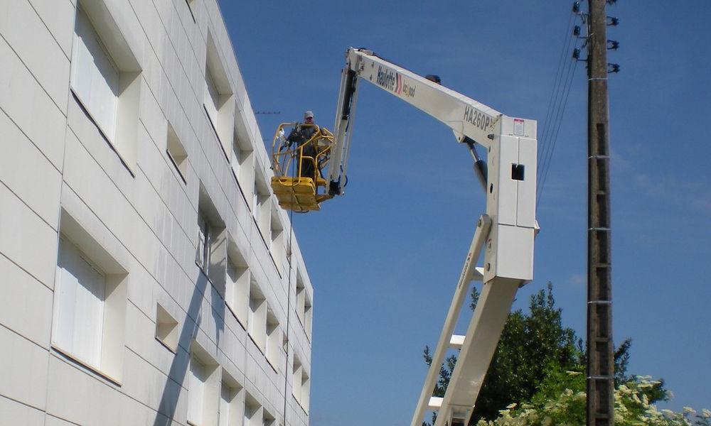 Nettoyage façade et toiture de bâtiment avec nacelle